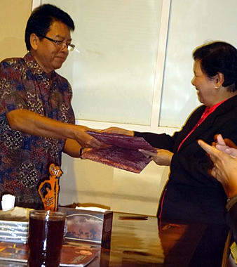 Prof. Dr. Wani Hadi Utomo, UNITRI Rector, and Dr. Elsa P. Manarpaac, WPU President, exchange their signed copies of their MOU