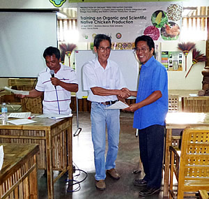 A participant receiving his certificate of completion from Dr. Arsenio D. Calub, Project Leader.