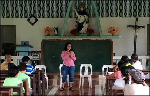 Dr. Bessie M. Burgos, SEARCA's head of Research, addresses  pressing issues and concerns raised by cooperative members and local  farmers in a local chapel used as assembly area in Malinao, Aklan.