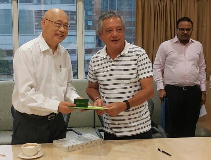 Dr. Saguiguit presents SEARCA briefing materials and a replica of the Growth Monument, SEARCA's institutional symbol, to Mr. Lim. Looking on is Mr. Vignesh Naidu, Research and Project Manager.