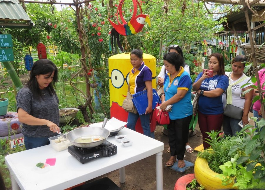 "Ms. Leticia Germina, one of the SHGP Coordinators of Pedro Guevara Memorial National High School, demonstrating to the participants her recipe called ""Lumpia con Tokwa't Alugbati""."