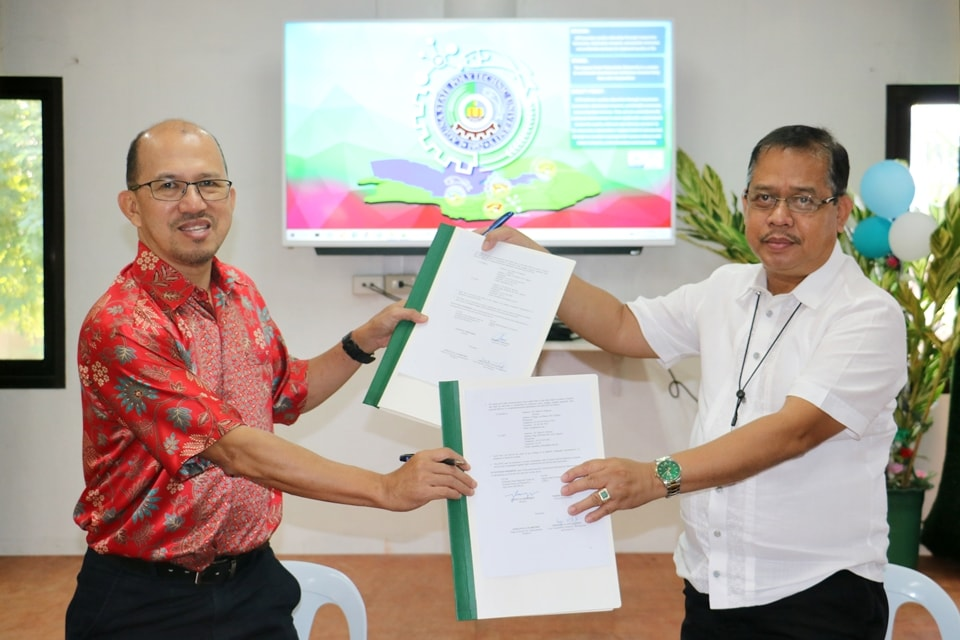SEARCA Director Dr. Glenn B. Gregorio (left) and LSPU President Dr. Mario R. Briones, exchange copies of the MOU between SEARCA and LSPU signed on 17 December 2020.