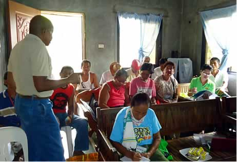 Prof. Williams (left) presents the outputs delivered by the SEARCA project team before the members of Farmer Vegetable Credit Cooperative during their special General Assembly on 11 August 2014 in Cabiao, Nueva Ecija.