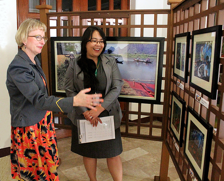 Ms. Avril D. Madrid, Program Specialist, Knowledge Resources (right), explains to the Ambassador some of winning photos of SEARCA's Photo Contest.