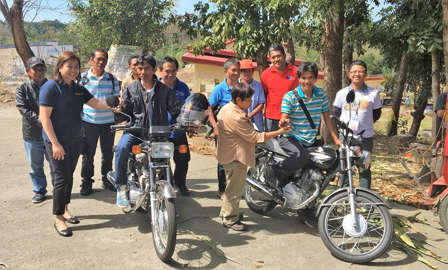 Ms. Nancy Landicho (leftmost), SEARCA Program Specialist, and Dir. Gloria Dela Cruz (front row, third from left), PCC Center Director at DMMMSU award the motorcycles to Mr. Rolly C. Mateo (on motorcycle, left), Chairman, BSNMPC; and Mr. Vicente Eblogan (on motorcycle, right), Treasurer of RDPA. | Back row (L-R): Mr. Fermin Q. Jamias, BOD; Mr. Leonardo Jamias, Treasurer; Mr. Edgar Niedo, Manager- all of BSNMPC; Mr. Reynaldo D. Paneda, SRA/AI Coordinator, PCC at DMMMSU; Mr. Victoriano P. Petina, Jr., President; Mr. Ricardo C. Eblogan, Sr. Vice President, all of RDPA; and Mr. Albert D. Nieva, staff of PCC at DMMMSU.
