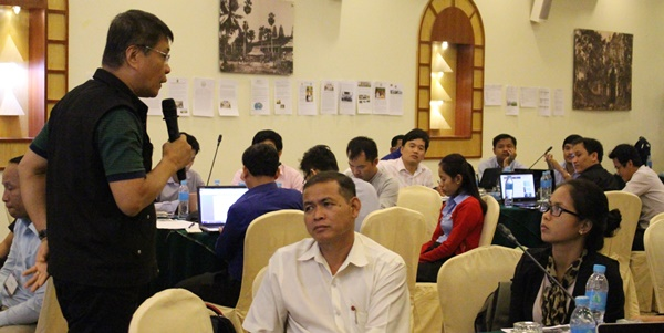 Participants listen to Dr. Navarro's point. Photo shows their articles and other workshop outputs posted on the wall for everyone's scrutiny.