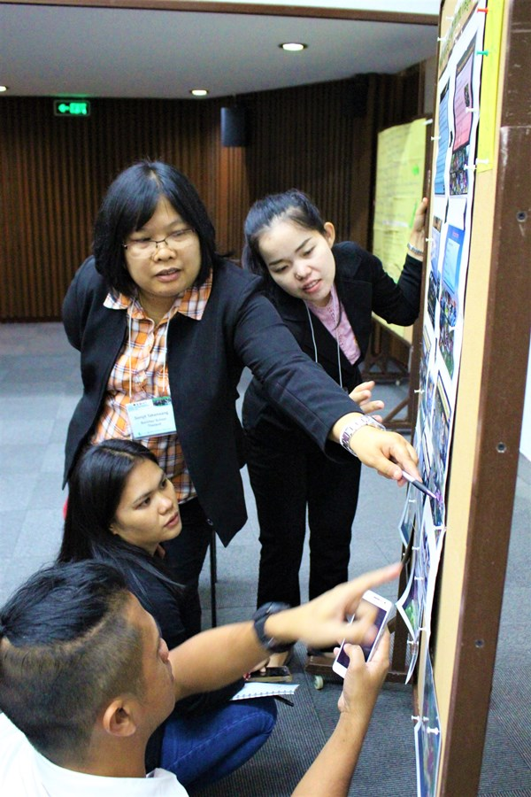 Participants from Thailand schools showcasing their initiatives related to school and home gardens using poster charts in the information marketplace.